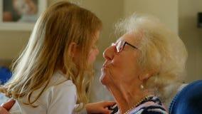 Großmutter und Enkelin, die im Wohnzimmer sich küssen stock video footage