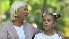 Großmutter und Enkelin, die sitzen und glücklich im Park, Familie sprechen stock footage