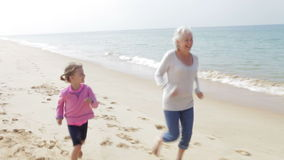Großmutter und Enkelin, die zusammen entlang Strand laufen stock video