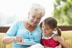 Großmutter-und Enkelin-Lesebuch auf Garten Seat lizenzfreie stockfotos