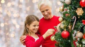 Großmutter und Enkelin am Weihnachtsbaum stockfoto