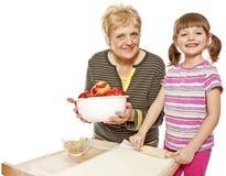 Großmutter- und Enkelinbackenapfelkuchen   lizenzfreie stockfotografie