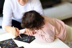 Großmutter- und Enkelinzeichnung zusammen mit Stock auf malendem Papier des magischen Kratzers zu Hause oder in der Klasse lizenzfreies stockbild