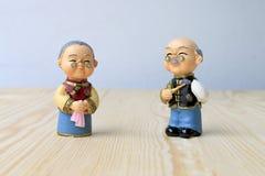 Großmutter- und Großvaterpuppen in der chinesischen einheitlichen Art, die auf hölzernem Hintergrund steht im chinesischen neuen  Stockfoto