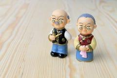 Großmutter- und Großvaterpuppen in der chinesischen einheitlichen Art, die auf hölzernem Hintergrund steht im chinesischen neuen  Lizenzfreies Stockbild
