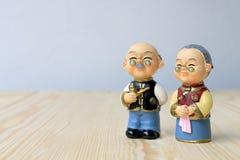Großmutter- und Großvaterpuppen in der chinesischen einheitlichen Art, die auf hölzernem Hintergrund steht im chinesischen neuen  Stockbilder
