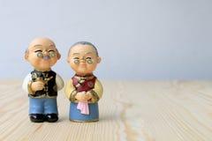 Großmutter- und Großvaterpuppen in der chinesischen einheitlichen Art, die auf hölzernem Hintergrund steht im chinesischen neuen  Stockbild