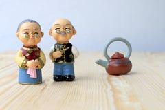 Großmutter- und Großvaterpuppen in der chinesischen einheitlichen Art, die auf hölzernem Hintergrund steht im chinesischen neuen  Lizenzfreie Stockfotos