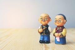 Großmutter- und Großvaterpuppen in der chinesischen einheitlichen Art, die auf hölzernem Hintergrund steht im chinesischen neuen  Stockfotografie