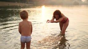 Großmutter und Kinderspiel in dem Meer, ein Spritzen des Wassers herstellend Unterhaltung und Spiele im Freien Langer Berührungss stock footage