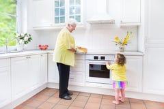 Großmutter und kleines Mädchen cookinga Torte in der weißen Küche Lizenzfreies Stockfoto