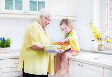 Großmutter und kleines Mädchen, die Torte in der weißen Küche kochen Lizenzfreies Stockfoto