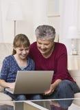 Großmutter und Mädchen mit Laptop Stockfotos