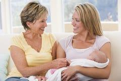 Großmutter und Mutter im Wohnzimmer mit Schätzchen Lizenzfreies Stockbild