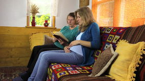 Großmutter und schwangere Enkelinfrau lasen Buch stock footage