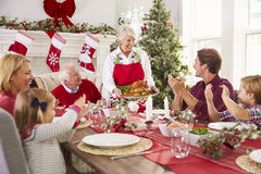 Großmutter, welche die Türkei an der Familien-Weihnachtsmahlzeit herausbringt Stockfotografie