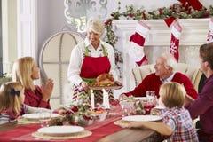 Großmutter, welche die Türkei an der Familien-Weihnachtsmahlzeit herausbringt Lizenzfreies Stockfoto