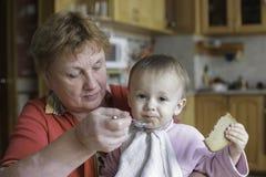 Großmutter zieht Baby mit Löffel ein Großeltern, Enkelkindlebensstilkonzept stockfotos