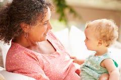 Großmutter zu Hause, die mit Enkelin im Garten spielt Stockbilder