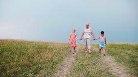 Großmutter in zwei Enkelkindern geht den ländlichen Weg hinunter steadicam Schuss stock footage