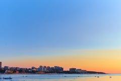 Großstadt durch das Meer bei Sonnenuntergang Stockfoto
