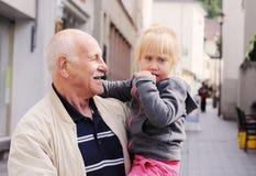 Großväterliche haltene Enkelin stockfoto