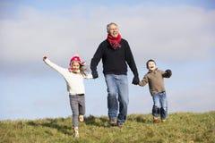 Großväterliche Holding-Hände mit seinen Enkelkindern Stockbilder