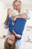 Großväterlicher haltener Enkel umgedreht zu Hause Stockfotos
