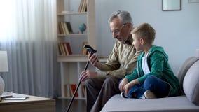 Großväterliches haltenes Telefon, Junge, der ihm zur Bekanntschaft mit neuen Technologien hilft lizenzfreies stockfoto