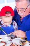 Großväterliches unterrichtendes Enkelkind, das mit Eisen lötet Lizenzfreie Stockfotos