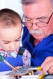 Großväterliches unterrichtendes Enkelkind, das mit Eisen lötet Lizenzfreies Stockbild