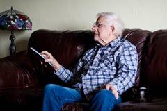 Großvater ändert Fernsehkanal mit Fernsteuerungs stockfotografie