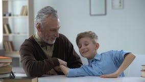 Großvater, der im Armdrücken mit dem Enkel, stolz auf Kind, Familienfreizeit gewinnt stock footage