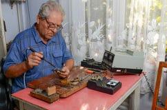 Großvater, der mit einem Lötkolben arbeitet Stockbilder