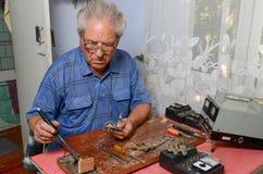 Großvater, der mit einem Lötkolben arbeitet Stockfoto