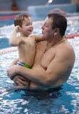 Großvater, der mit seinem Enkel in einem Swimmingpool spielt Lizenzfreies Stockfoto