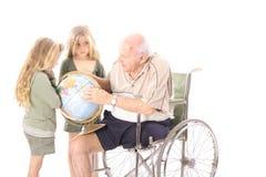 Großvater, der seinen Enkelkindern die Kugel zeigt Lizenzfreie Stockbilder