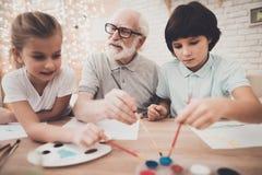 Großvater, Enkel und Enkelin zu Hause Kinder malen lizenzfreie stockfotos