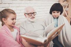 Großvater, Enkel und Enkelin zu Hause Großvater und Kinder passen Fotos im Album auf Lizenzfreie Stockfotos
