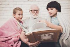 Großvater, Enkel und Enkelin zu Hause Großvater und Kinder passen Fotos im Album auf Lizenzfreies Stockbild