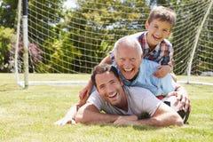 Großvater-, Enkel-und Vater-With Football In-Garten Lizenzfreie Stockbilder