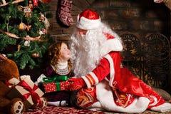 Großvater Frost gibt einem Geschenk ein kleines Mädchen lizenzfreie stockfotografie