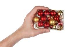 Großvater hält in seinem Handplastikkasten mit Weihnachtsbällen lokalisiert lizenzfreie stockfotografie
