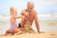 Großvater-kleines blondes Mädchen-Jungen-Gestalt-Sandburg auf Strand Stockfotos