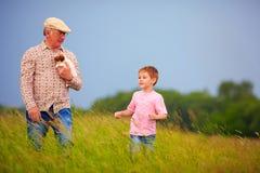 Großvater mit dem Enkel, der durch das Sommerfeld geht Stockbilder