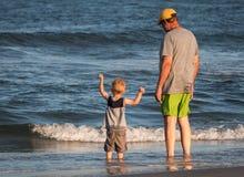 Großvater mit Enkel auf Strand Stockfotos
