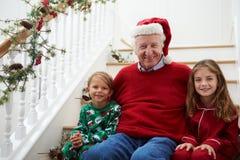 Großvater mit Enkelkindern sitzt auf Treppe am Weihnachten Lizenzfreie Stockfotos