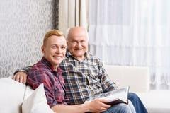 Großvater und Enkel, die mit Album sitzen Lizenzfreie Stockbilder