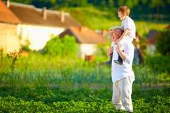 Großvater und Enkel, die Spaß auf ihrem Gehöft haben Stockfotografie