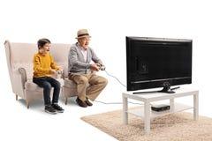 Großvater und Enkel, die Videospiel vor einem Fernsehen spielen stockbilder
